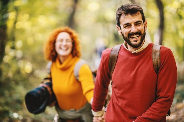 手をつないで自然の中を歩くカップル。人への選択的な焦点。