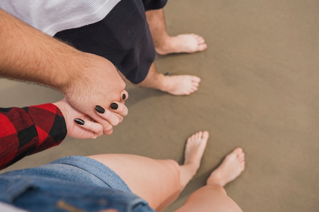 Couple holding hands on beach with bare feet