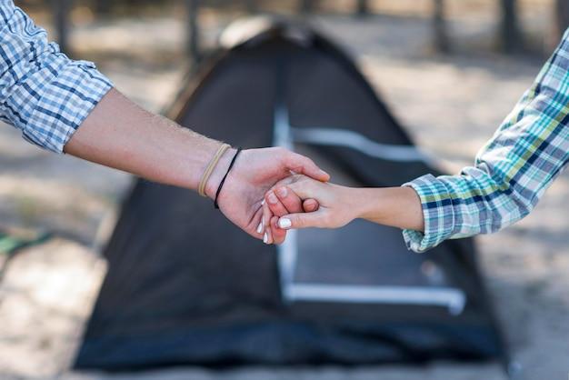 Coppia tenendosi per mano offuscata tenda