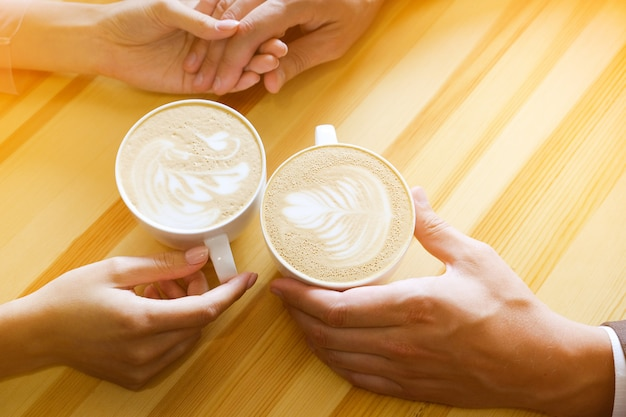 Couple holding hands in cafe, hands of lovers. guy and girl holding mugs of coffee.