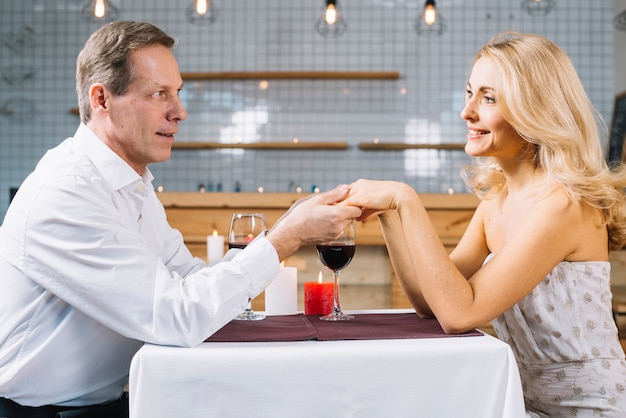 Couple holding hands during dinner