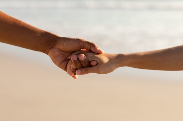 Couple holding hands of each other on the beach