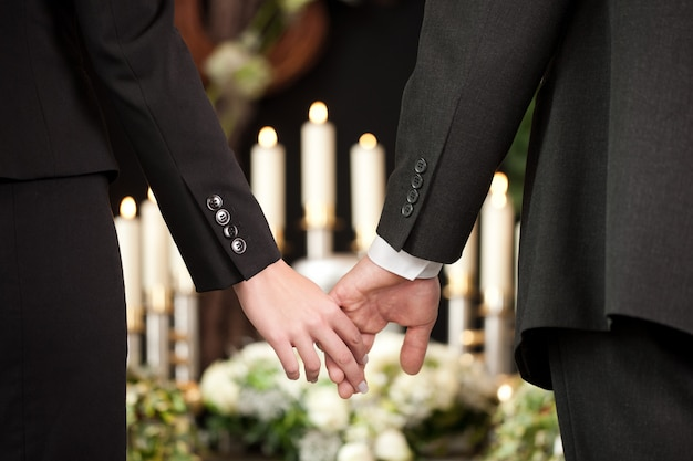 Couple holding hands at a funeral