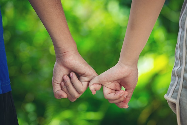 Couple holding hands in green meadow.