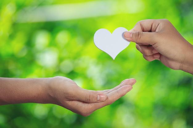 Coppia mano nella mano nel prato verde.