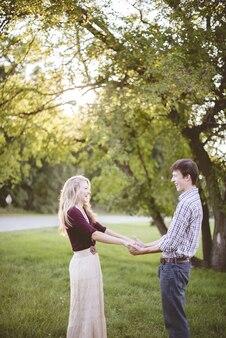 日光の下で緑に囲まれた庭で手を繋いでいるカップル