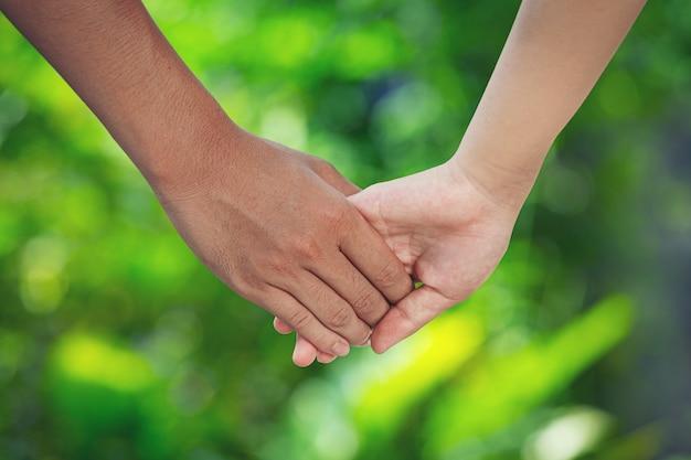 Пара, взявшись за руки на зеленом лугу.