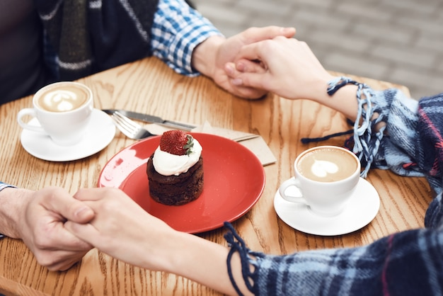 Couple in holding hands love cappuccino cupcake.