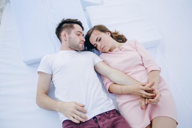 Пара, держась за руки, лежа на кровати и двойной она спит