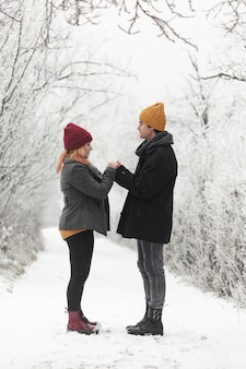 Couple holding hands outdoors long view