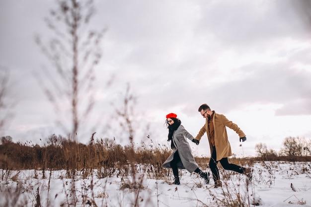Couple holding hands running through a winter park