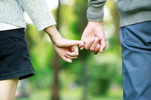 Пара, взявшись за руки, показывает любовь в день святого валентина