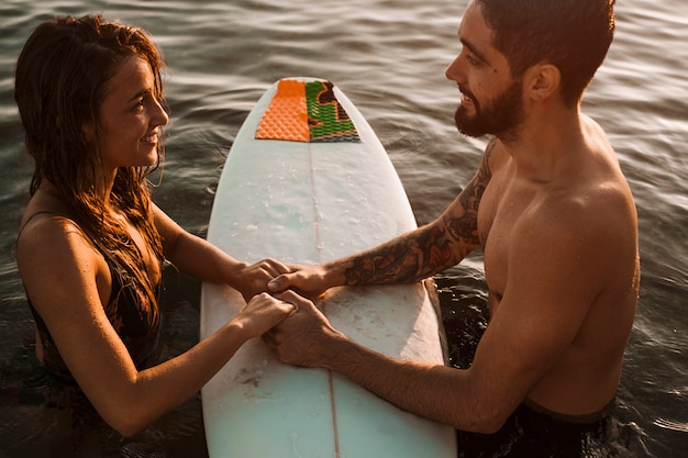 Couple holding hands on surfboard