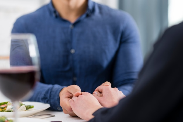 Couple holding hands on table close-up