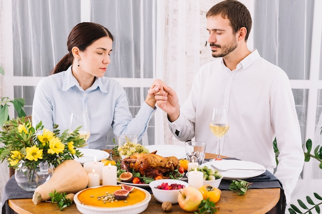 Couple holding hands at table with food