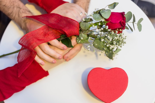 Couple holding hands on table with rose