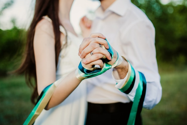 Couple holding hands tied up with ribbon