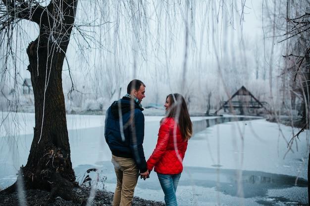 Пара, держась за руки под снежное дерево
