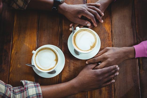 Пара, держащая руки, имея кофе