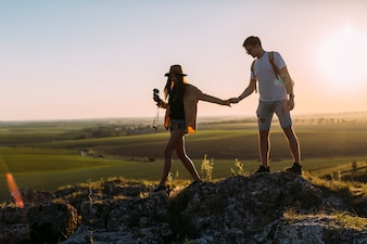 Couple holding hands while hiking on rock