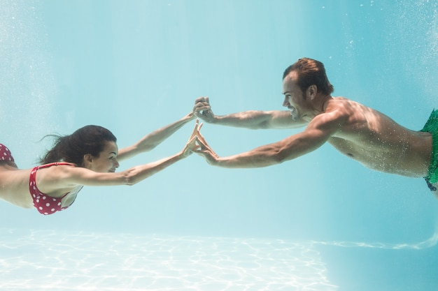 Couple holding hands while swimming underwater