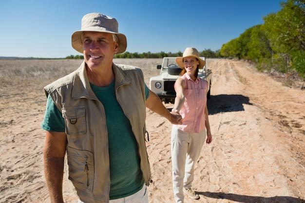 風景の上を歩きながら手を繋いでいるカップル