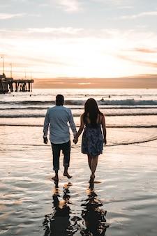 낮 동안 해변을 걷는 동안 서로 손을 잡고 커플