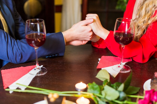 Couple holding hands at wooden table in restaurant