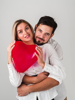 Couple holding heart balloon and posing