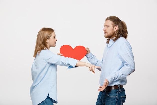灰色に対して怒っている表情を持つ心臓の形の紙を持っているカップル。