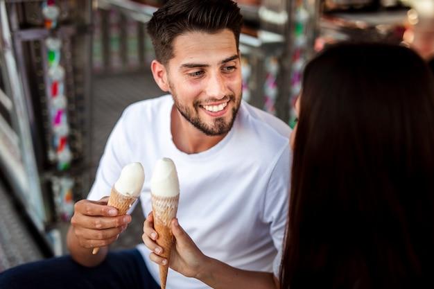 お互いを見てアイスクリームを保持しているカップル