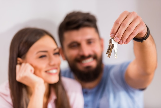 Couple holding keys to new home, moving to a new home.