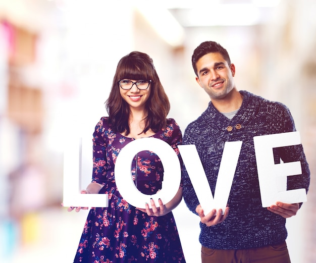 Couple holding letters that says
