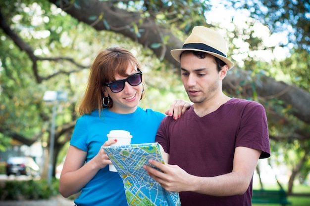 Couple holding map in hands and traveling together.
