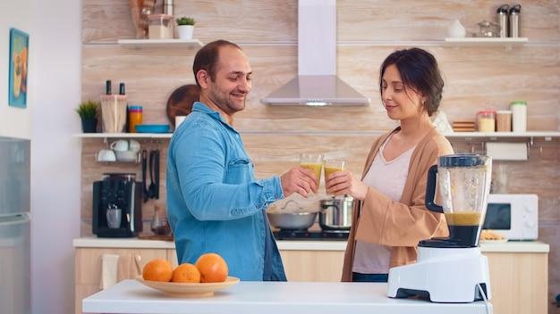 Пара, держащая питательный коктейль на кухне из вкусных фруктов. веселая семья делает вместе органические здоровые свежие питательные вкусные соки на завтрак из свежих фруктов во время диеты.