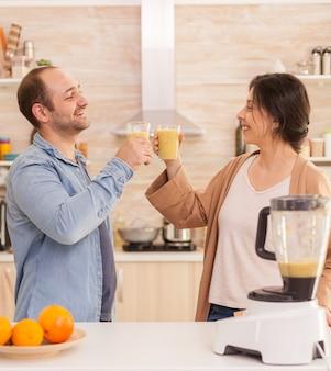 맛있는 과일로 부엌에서 영양가 있는 스무디를 들고 있는 커플. 건강하고 평온하고 쾌활한 생활 방식, 다이어트를 먹고 포근하고 화창한 아침에 아침 식사를 준비합니다.