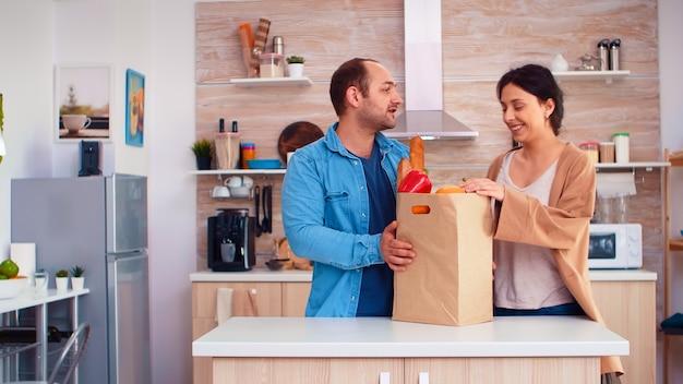 キッチンでスーパーマーケットからの食料品と紙袋を保持しているカップル。陽気な幸せな家族の健康的なライフスタイル、新鮮な野菜や食料品。スーパーマーケットの商品ショッピングライフスタイル