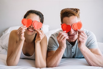 Couple holding paper hearts on eyes