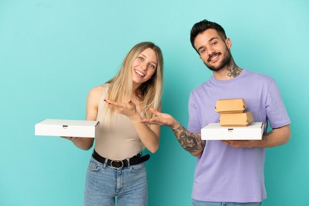 격리된 파란색 배경 위에 피자와 햄버거를 들고 있는 커플이 초대하기 위해 손을 옆으로 내밀었습니다.