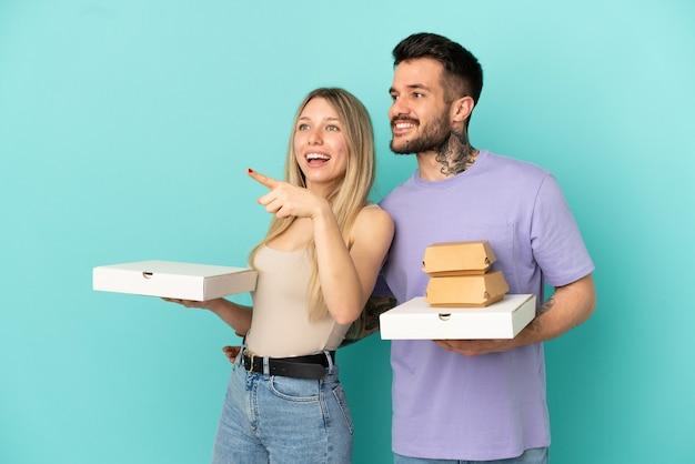 제품을 제시하기 위해 측면을 가리키는 고립된 파란색 배경 위에 피자와 햄버거를 들고 있는 커플