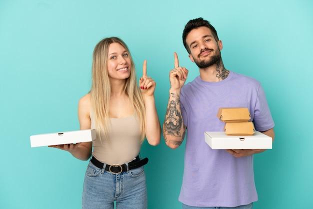 격리된 파란색 배경 위에 피자와 햄버거를 들고 있는 커플이 최고라는 표시로 손가락을 들고 들어올립니다.
