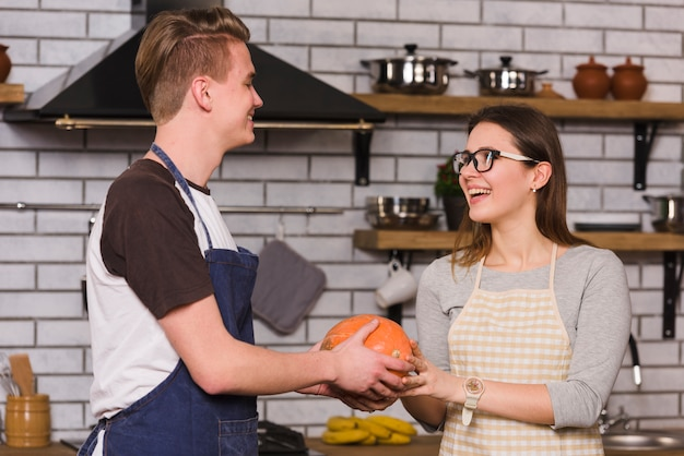 Couple holding pumpkin together standing in kitchen