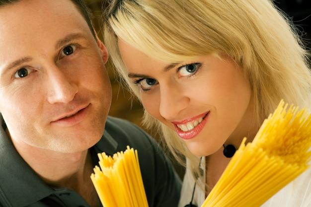 Couple holding raw pasta
