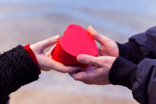 Couple holding small gift box in heart shape