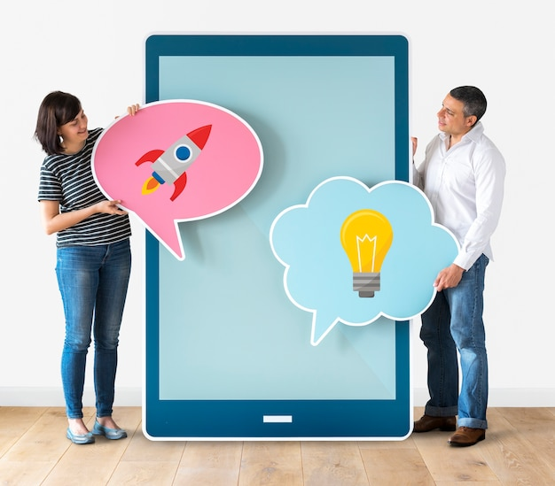 Couple holding speech bubbles and tablet