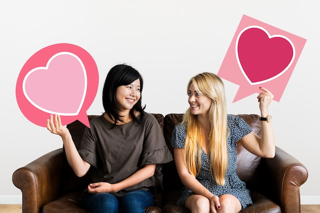 Couple holding speech bubbles with heart icons