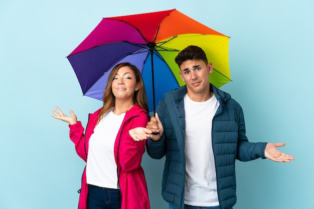 Couple holding an umbrella on blue having doubts while raising hands and shoulders