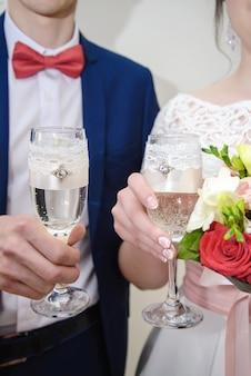 シャンパンと結婚式のグラスを保持しているカップル