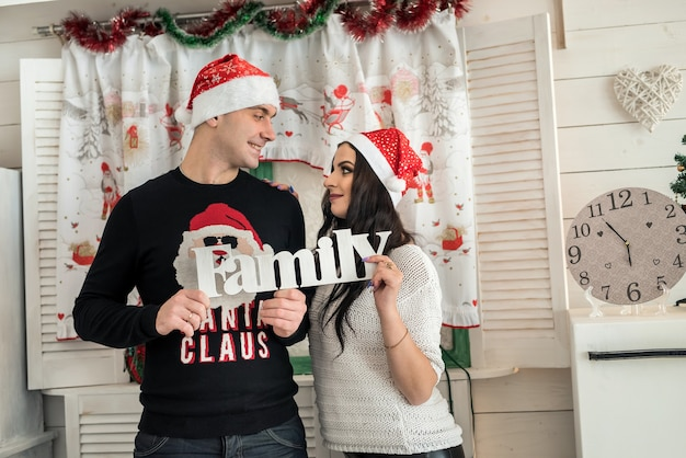 Couple holding word 'family' and looking at each other
