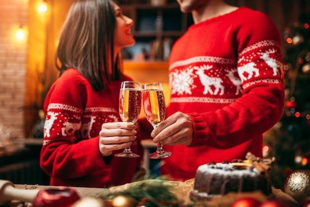 カップルは、シャンパン、クリスマスのグラスを保持しています。